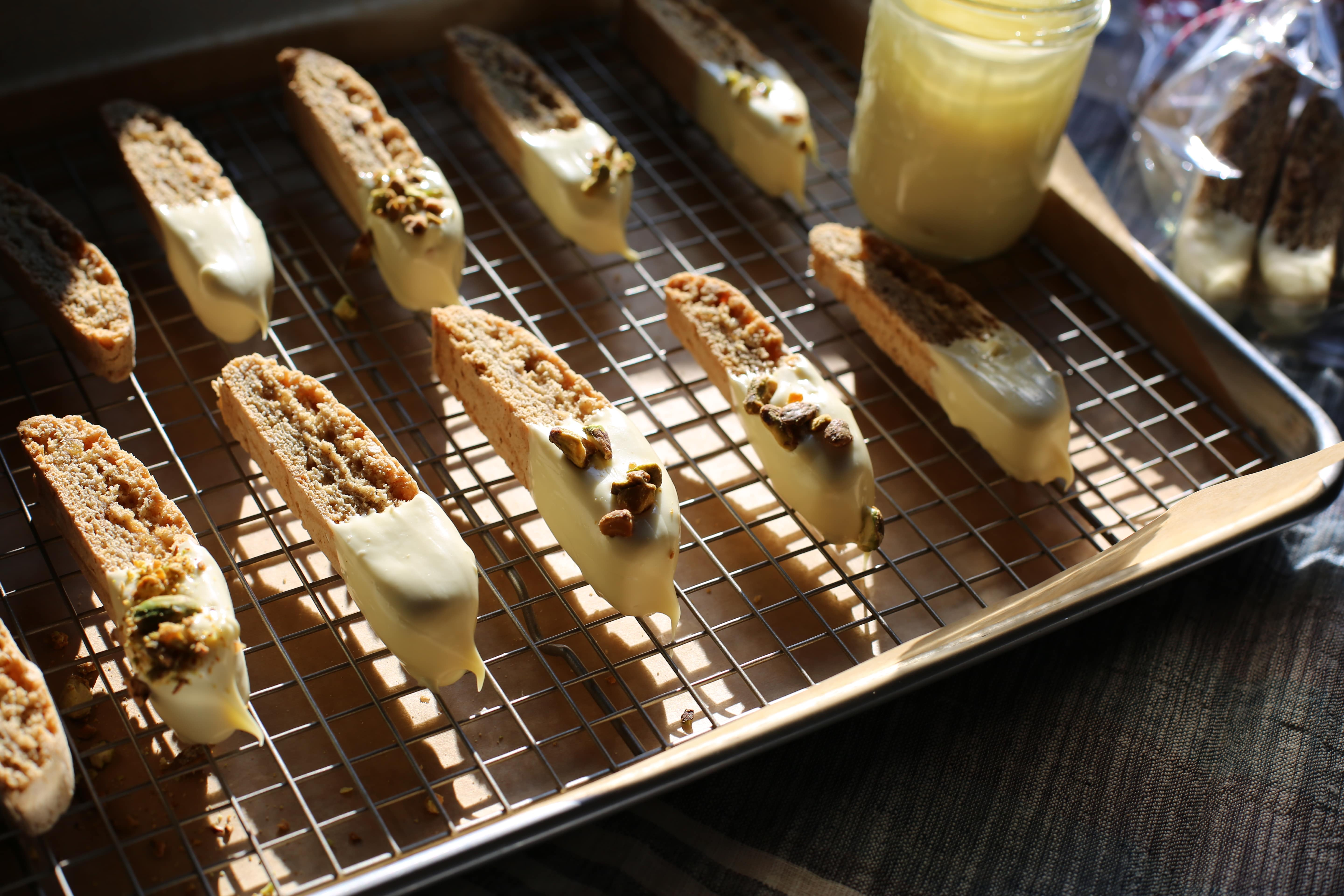 a baking sheet of biscotti with a glass jar of melted white chocolate next to it for dipping.