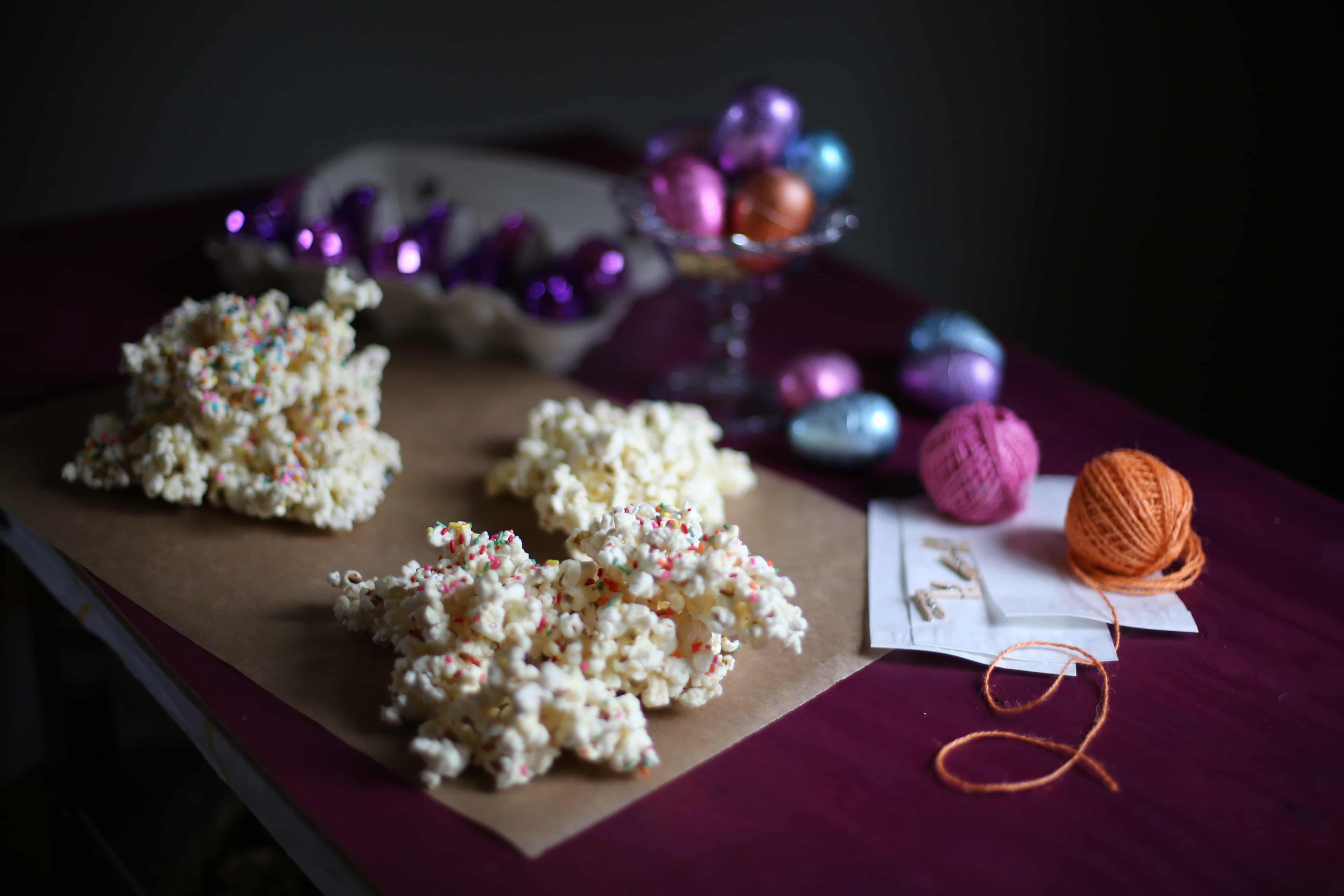 popcorn on a wooden table with decorations behind it