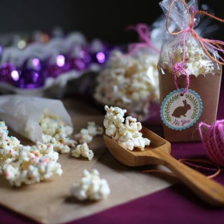 popcorn on a table with a wooden spoon