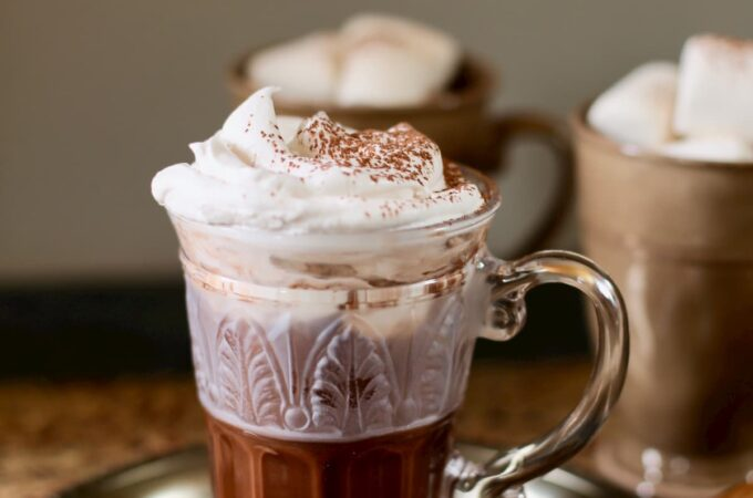 hot chocolate on a table with two other cups with marshmallows
