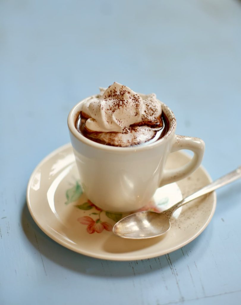 hot chocolate in a white cup with a silver spoon