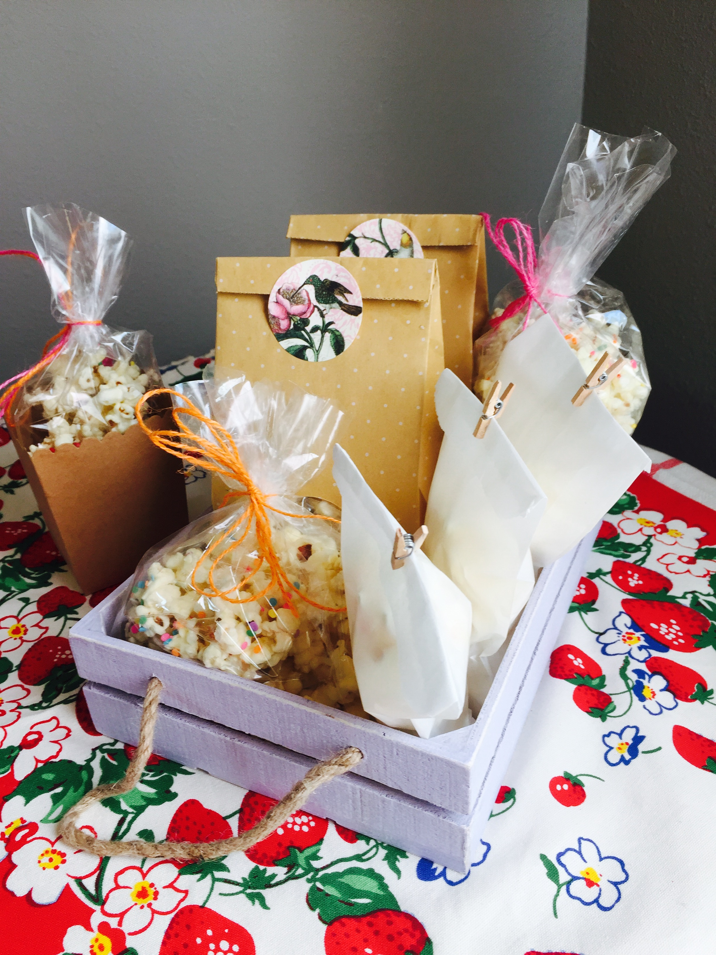 bags of white chocolate popcorn in a purple crate for gifting
