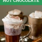 glass of hot chocolate on a table with wooden spoon