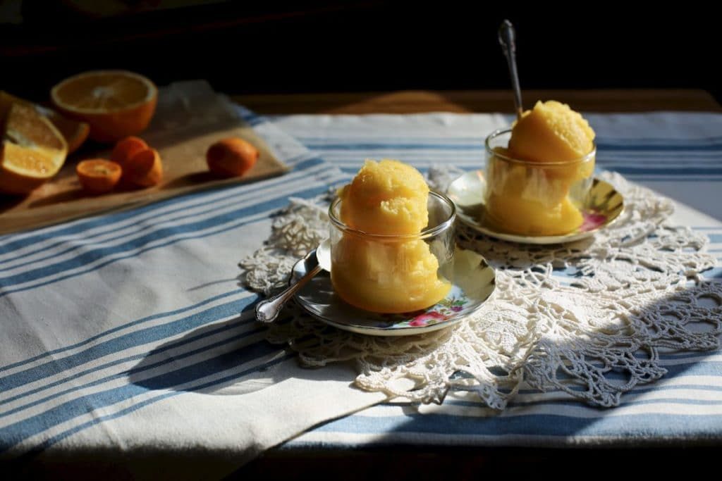 two cups of sorbet on a table with lace and oranges