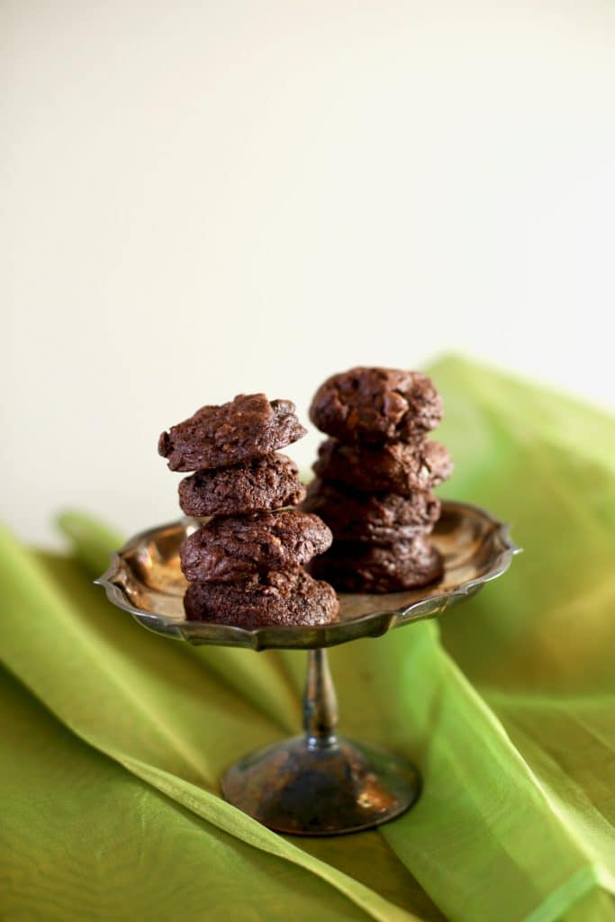 chocolate cookies on a silver tray with green background