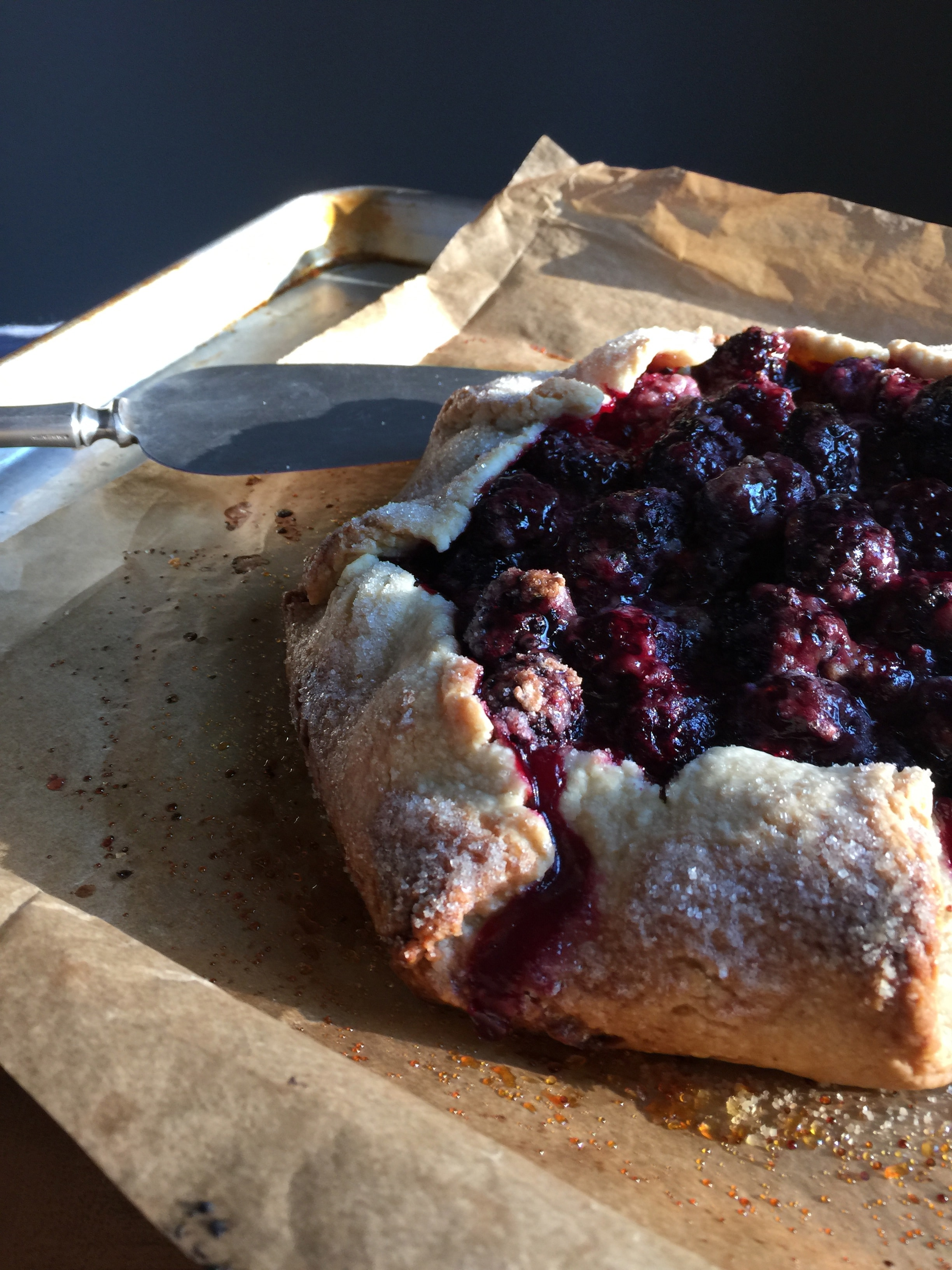 a close-up shot of a blackberry galette on a baking sheet with parchment paperte and a serving utinsil