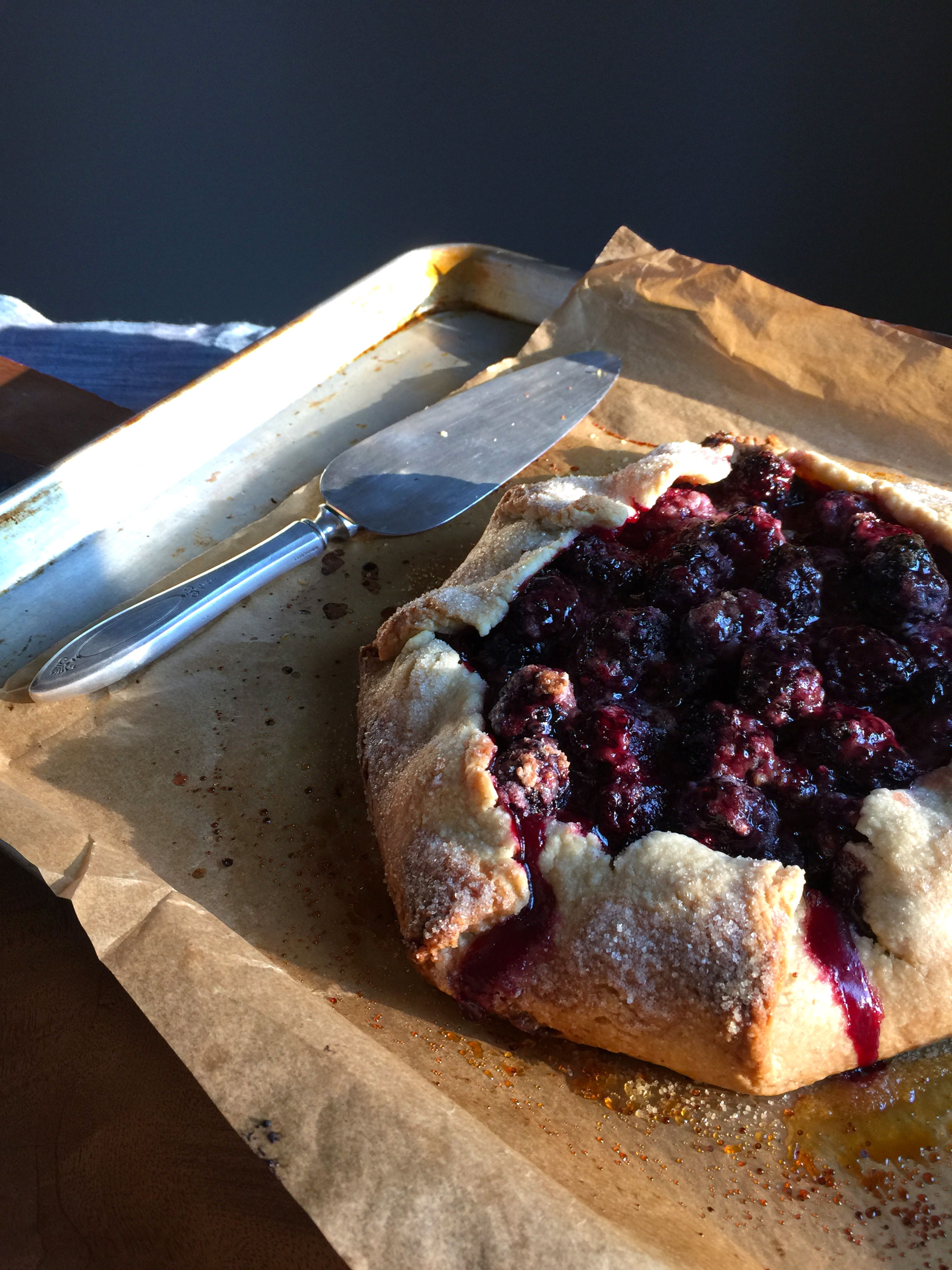 a galette/tart sitting on a baking sheet with a serving utinsil