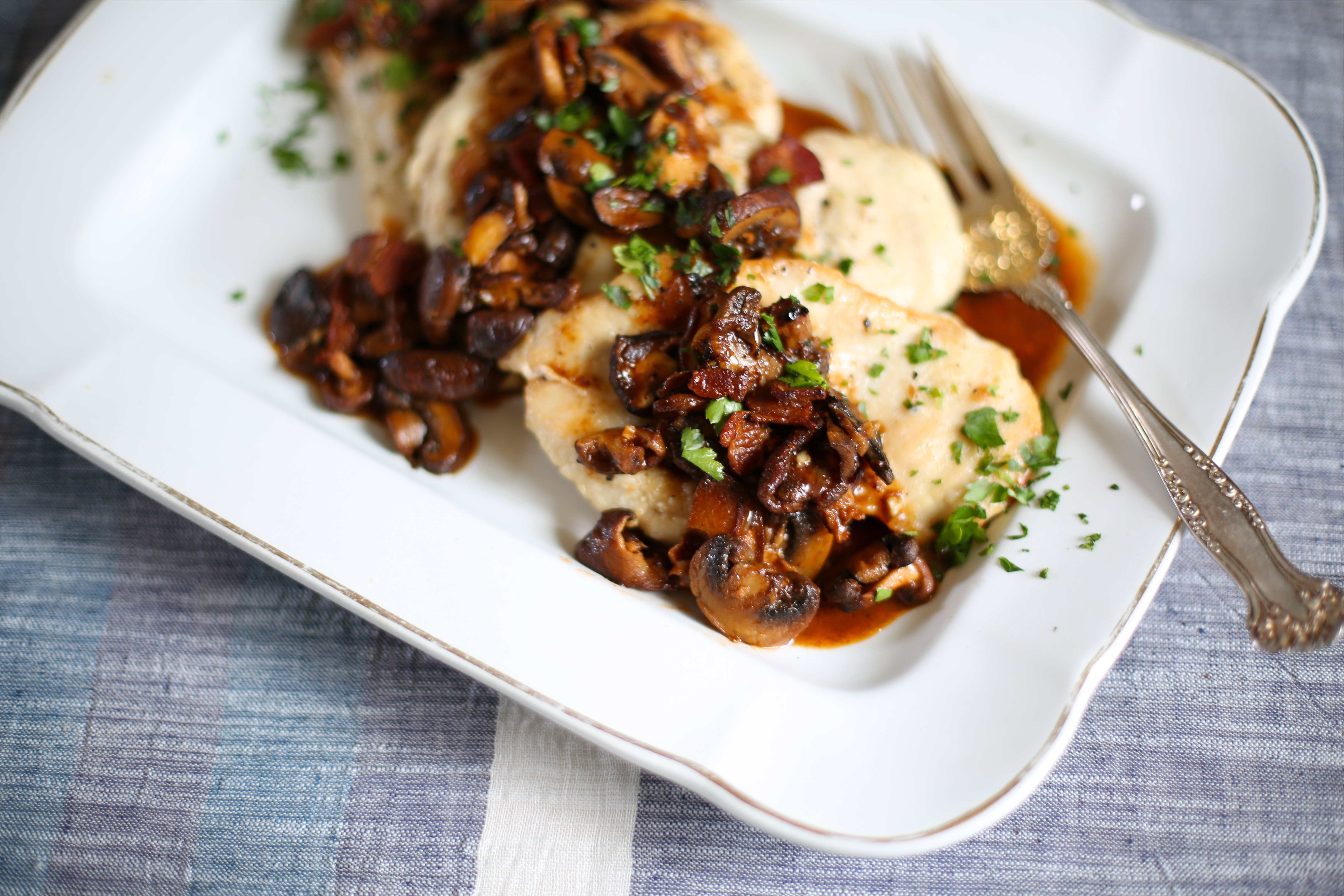 Several pieces of Chicken Marsala on a serving platter with a silver serving fork