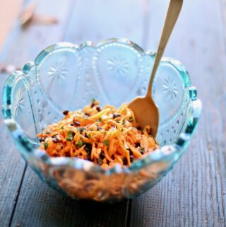 carrot salad in a blue bowl in a wood table