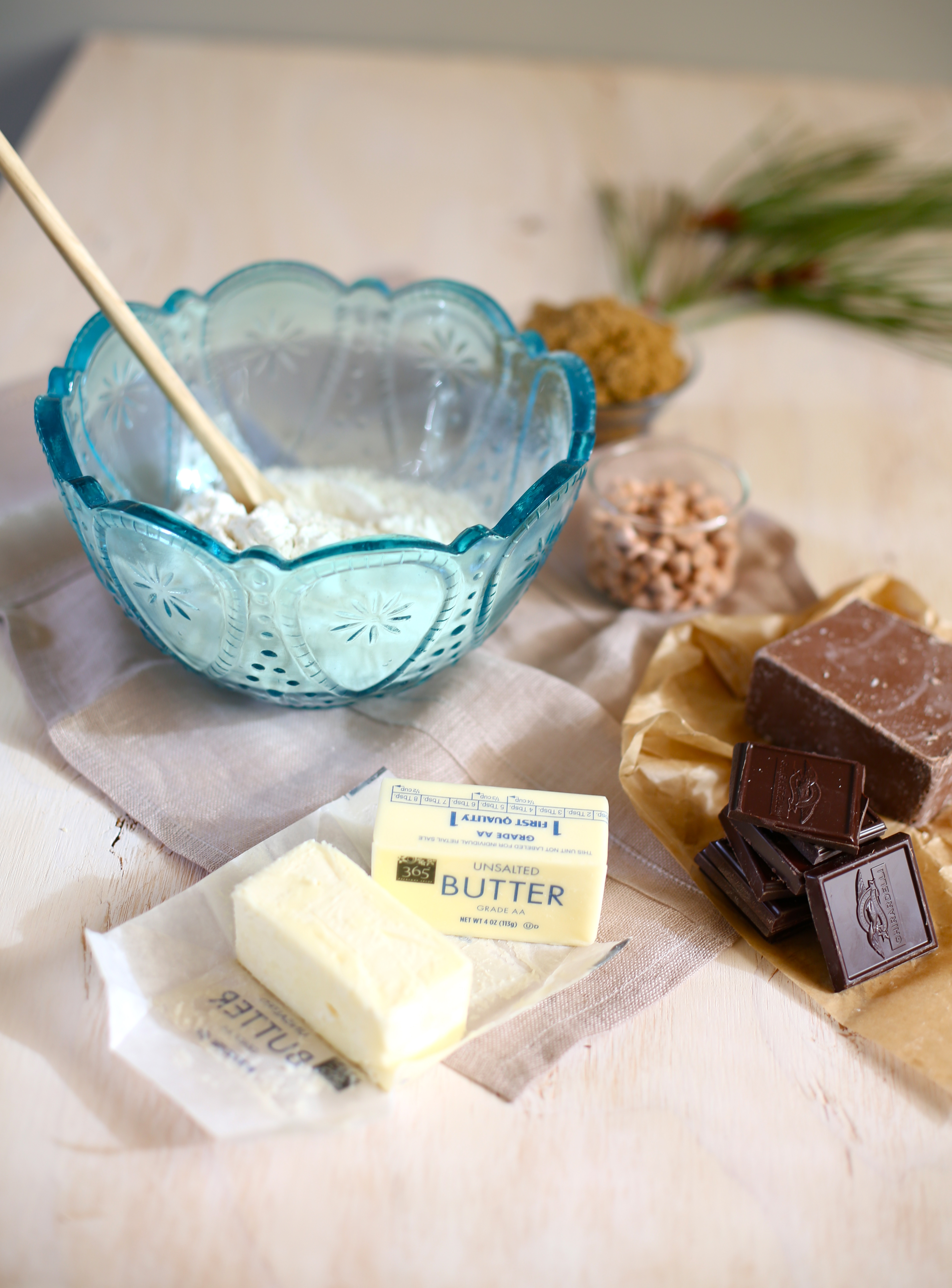 Ingredients for cookies on a table with a blue bowl, butter, chocolate and other ingredients
