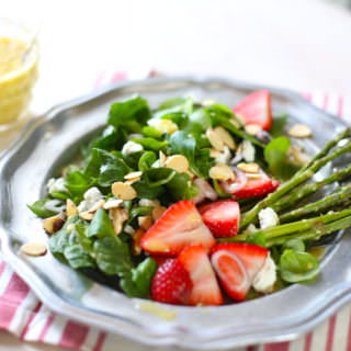green salad on a plate woth fresh strawberries