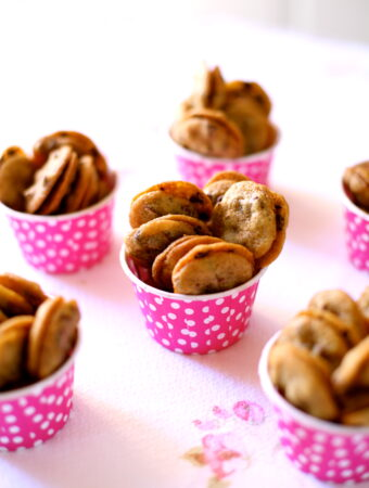small cookies in pink cups on a table