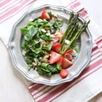 green salad and dressing on a silver plate with striped tablecloth