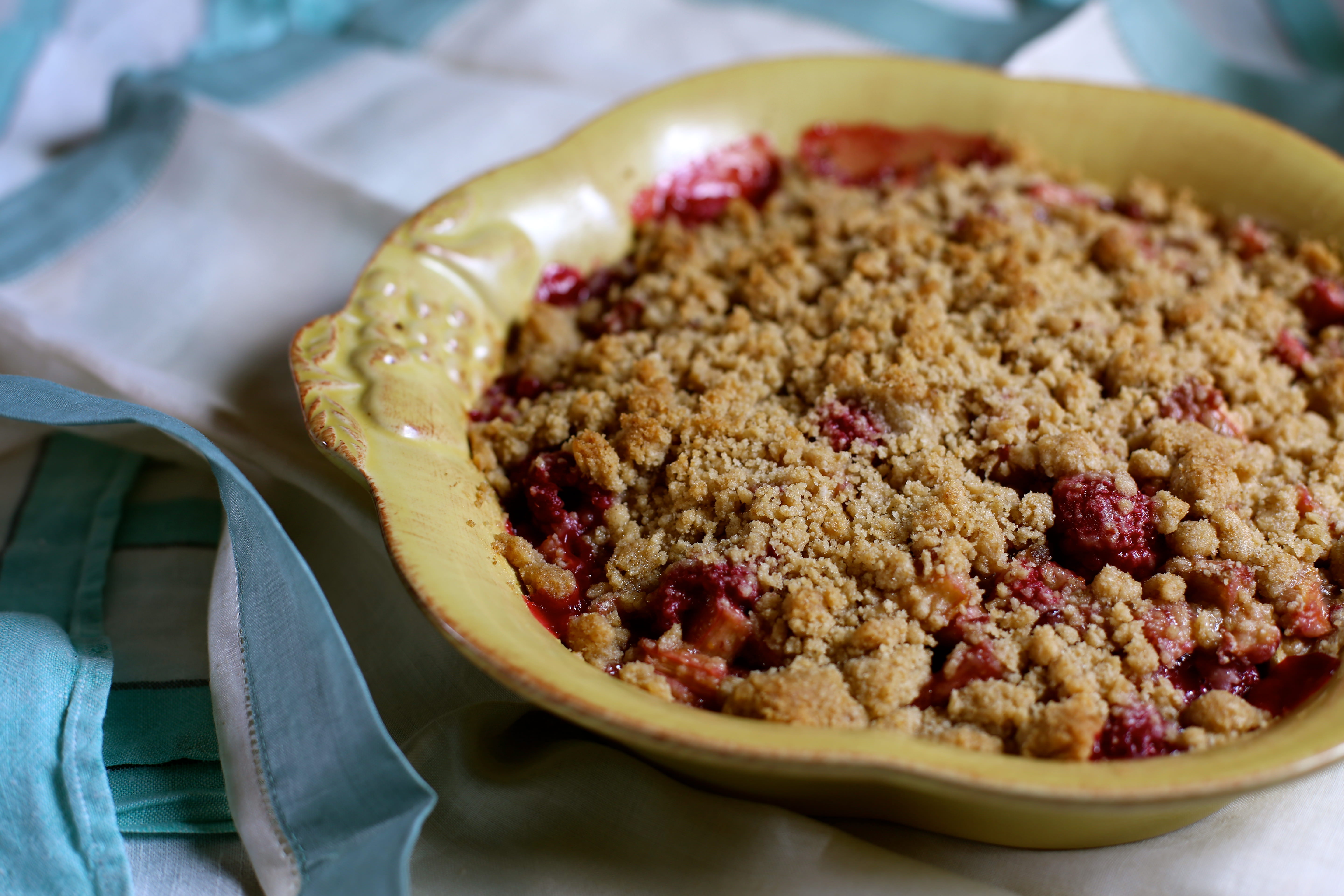 A yellow baking dish of Raspberry Rhubarb Crisp on a blue and white table cloth
