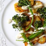 broccolini and potatoes on a white platter