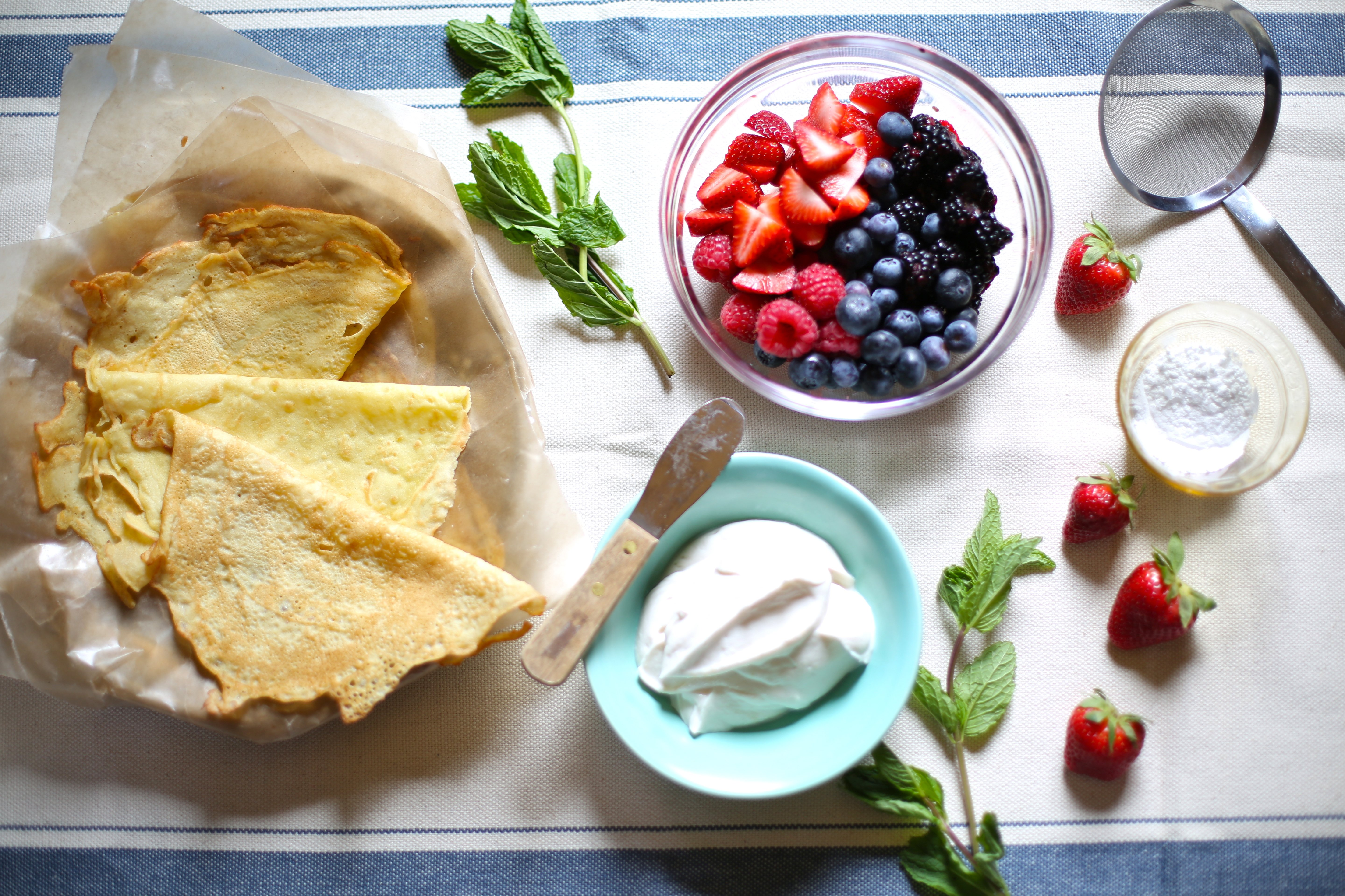 ingredients for crepes and berries and cream on a table, ready for serving.