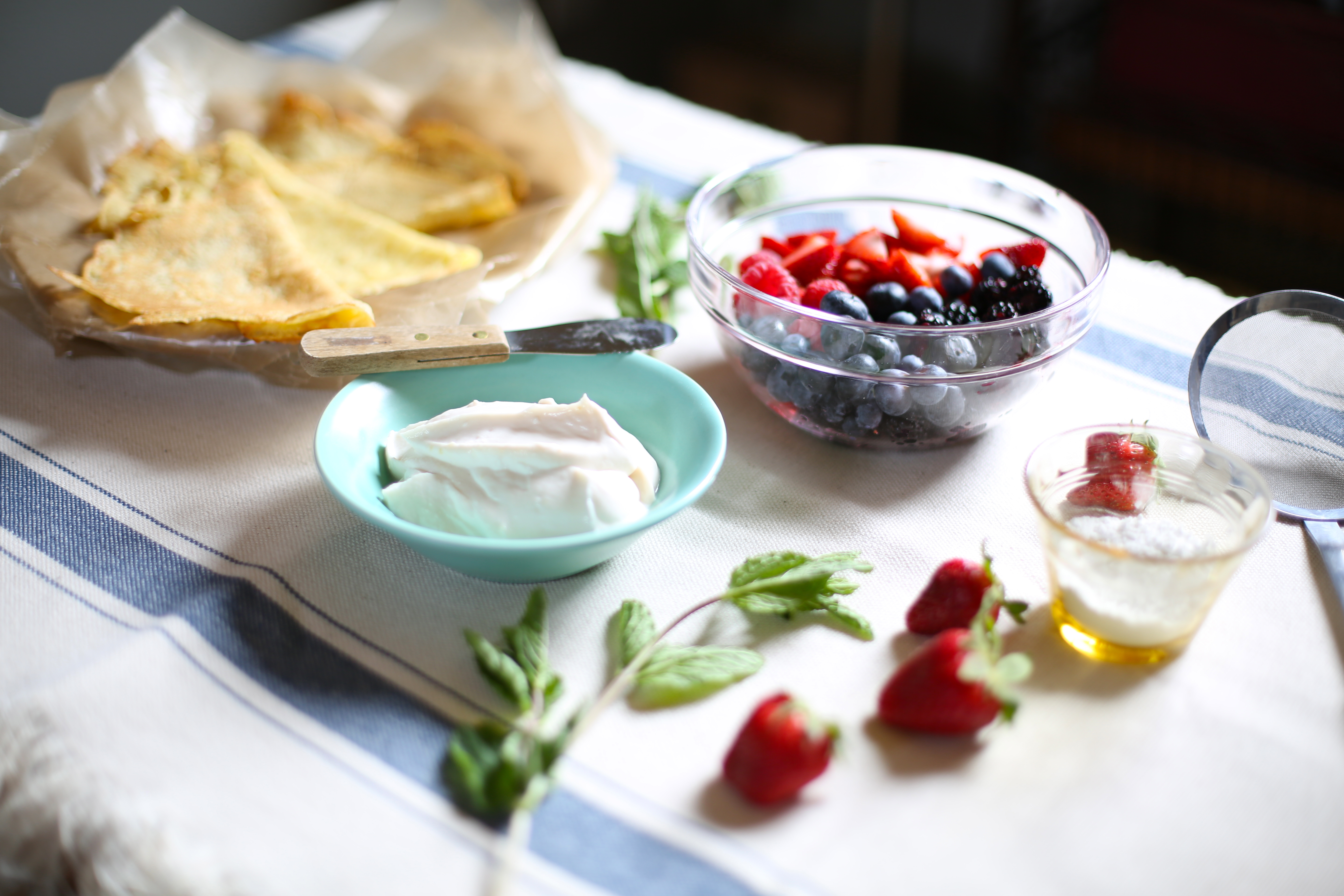 The ingredients for crepes with fresh fruit on a table.