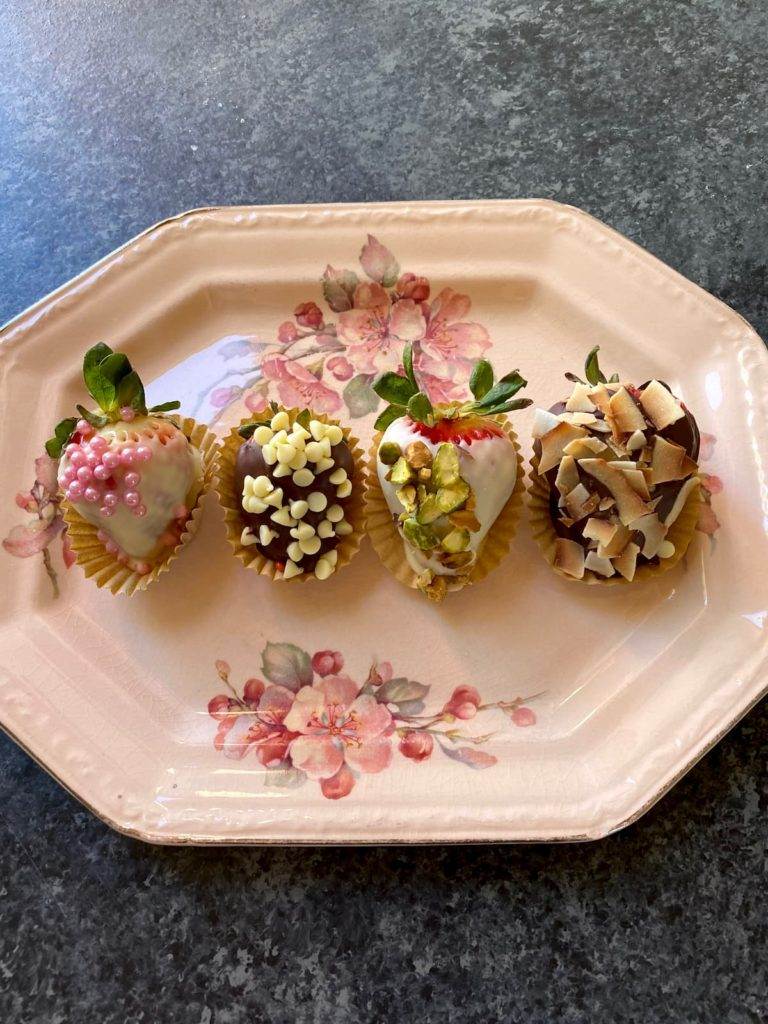 four chocolate dipped strawberries on a flowered pink plate