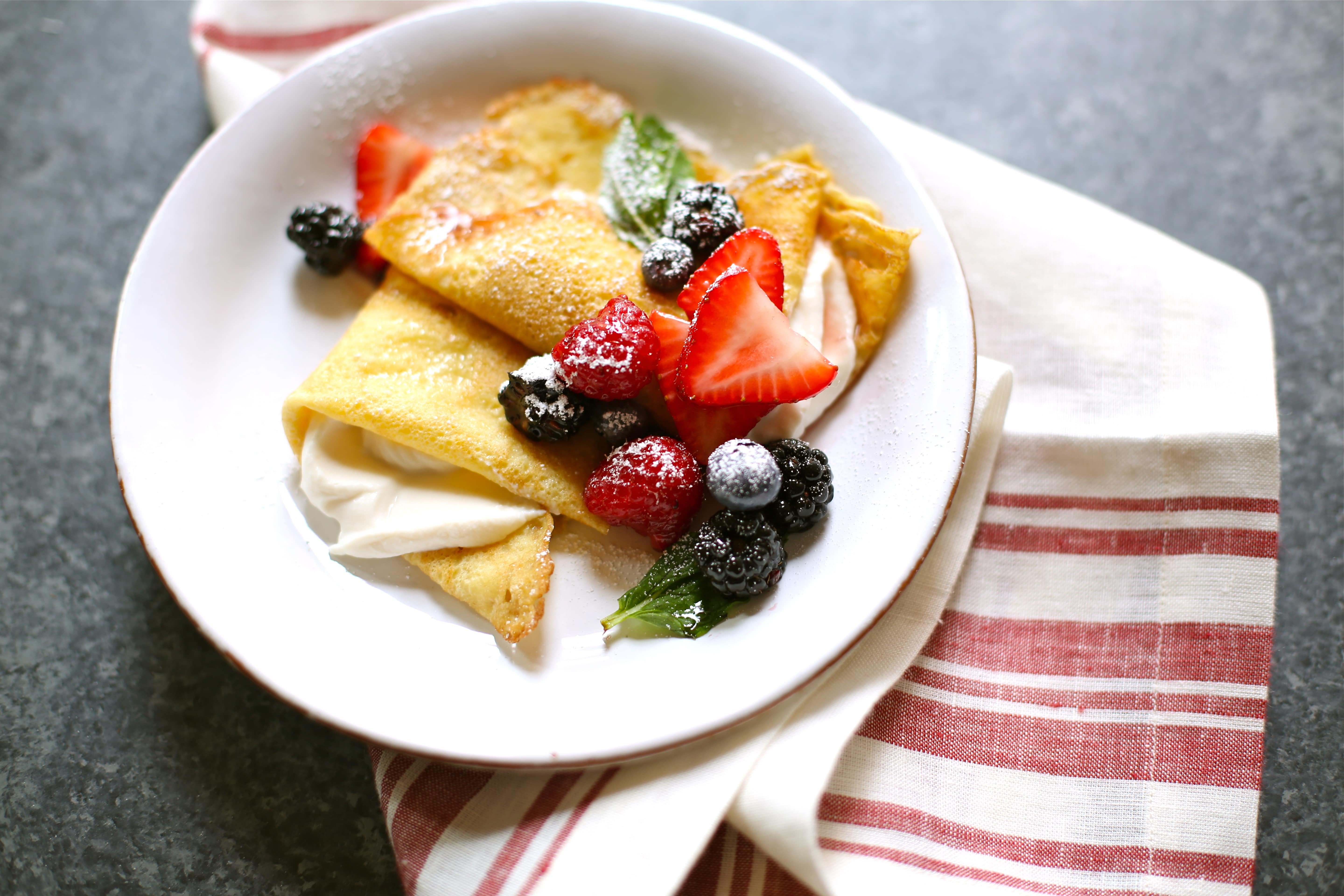 a plate of crepes with fresh fruit and cream on a black table with a striped red napkin.
