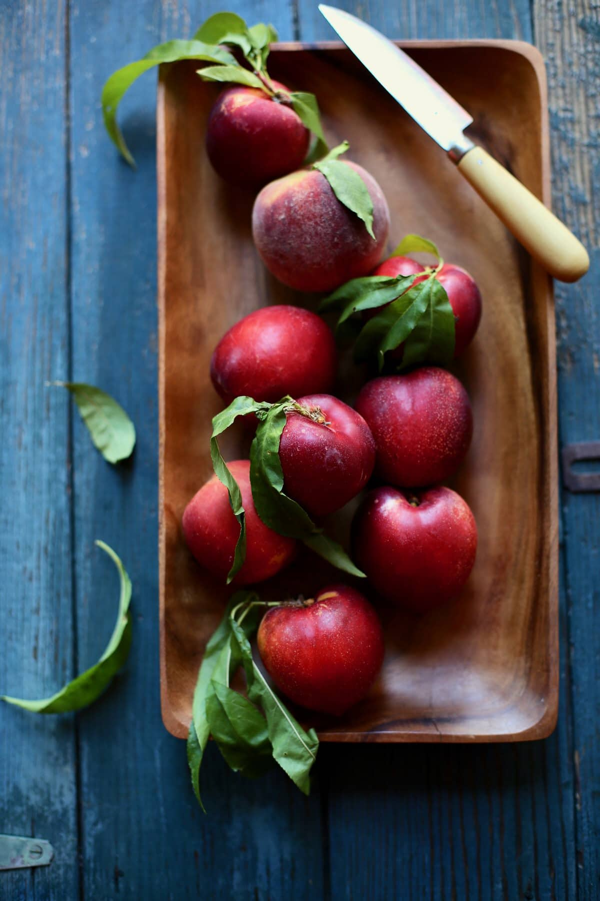A wooden tray of nectarines on a blue table with a knife sitting next to it