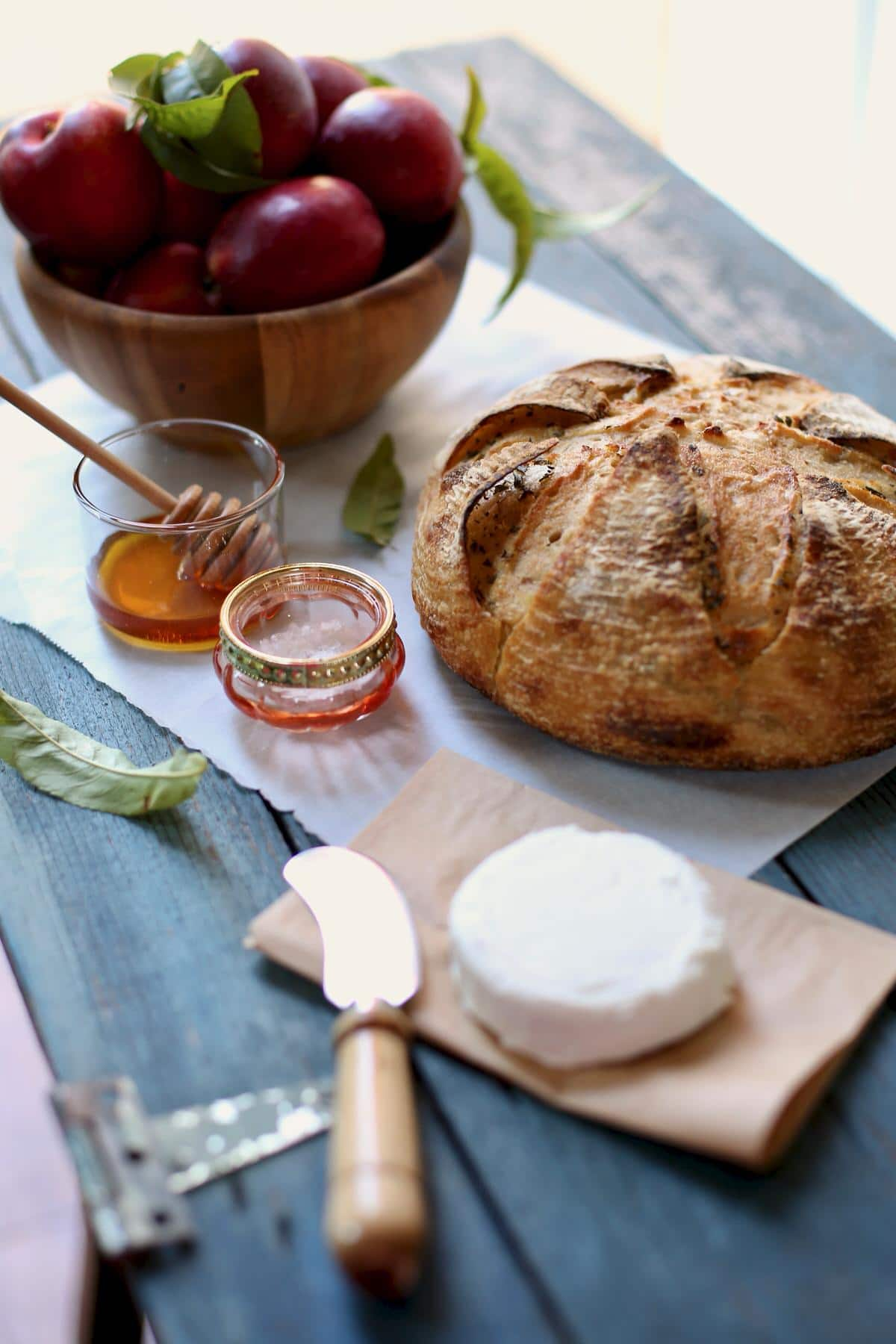 Fresh bread and goat cheese and honey on a table with a honey dipper and cheese spreading knife and small wooden bowl.