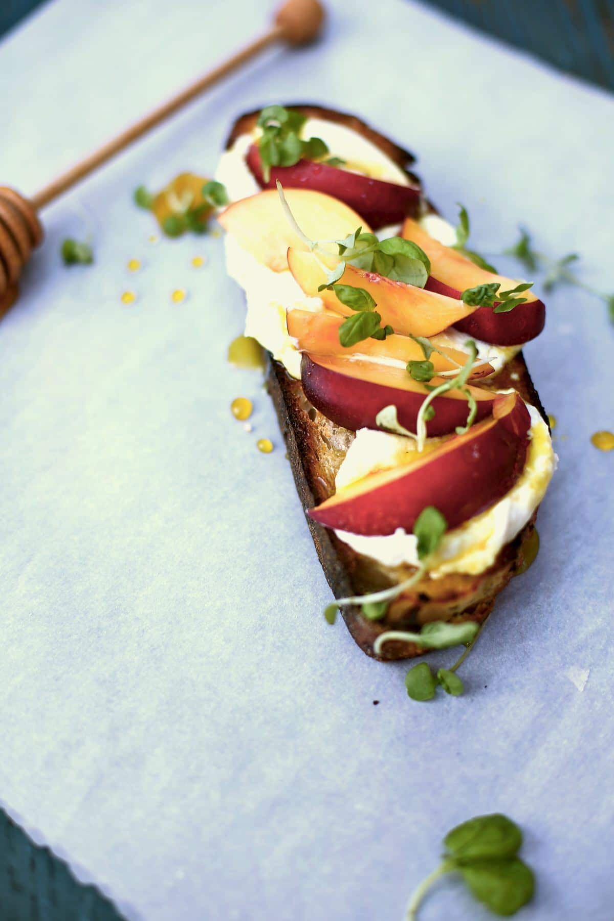a big slice of toast with nectarines and honey and goat cheese and basil  on a white table with a honey dipper sitting nearby.