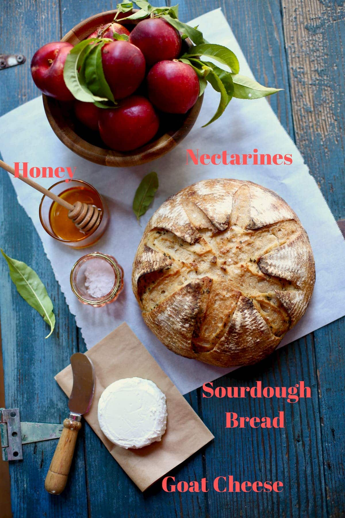 A round of bread, goat cheese, nectarines, honey, flaky sea salt and parchment paper sitting on a blue wooden table