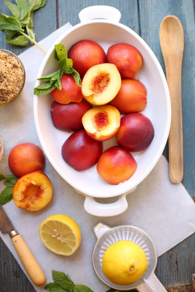 Nectarines with mint and lemon and brown sugar and a knife and spoon on a blue wood board