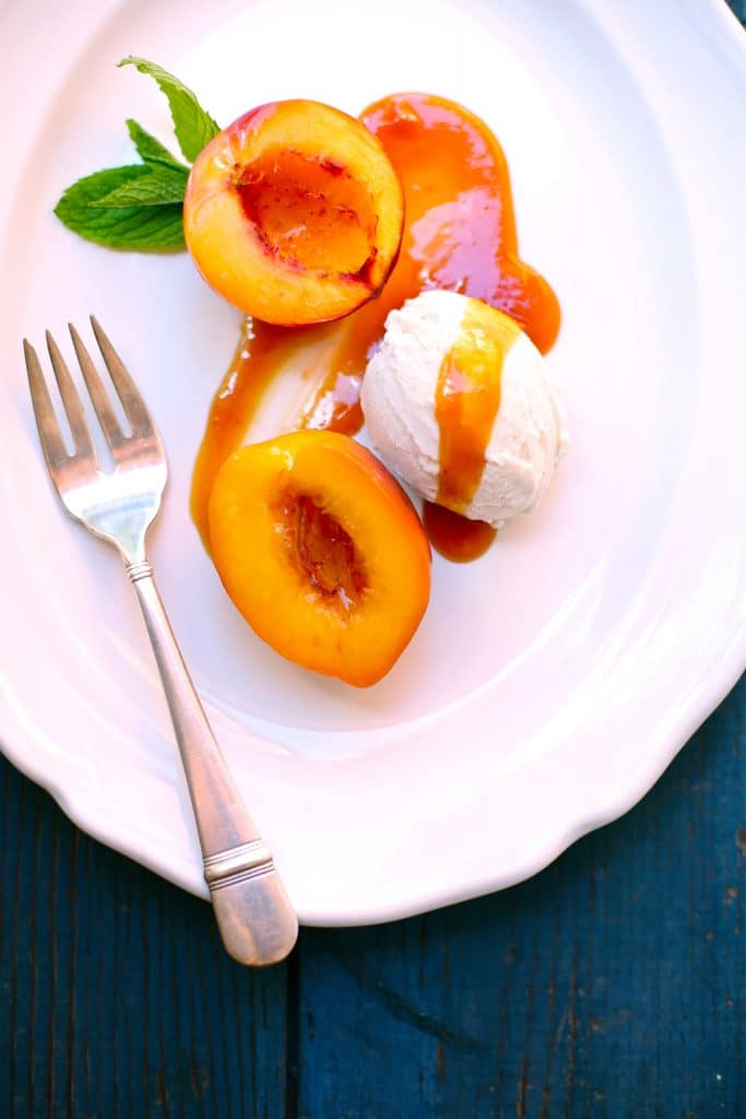 Roasted Nectarines with Caramel Sauce on a white plate with a fork