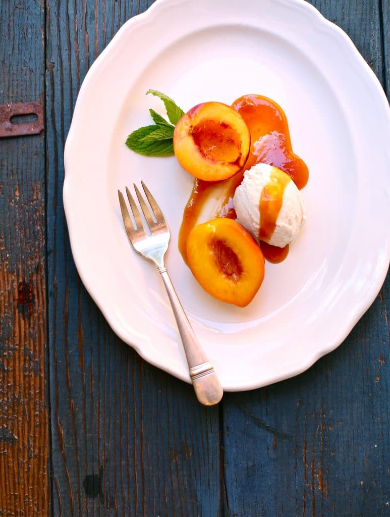 Roasted Nectarines with Caramel Sauce on a blue wood table with a silver fork