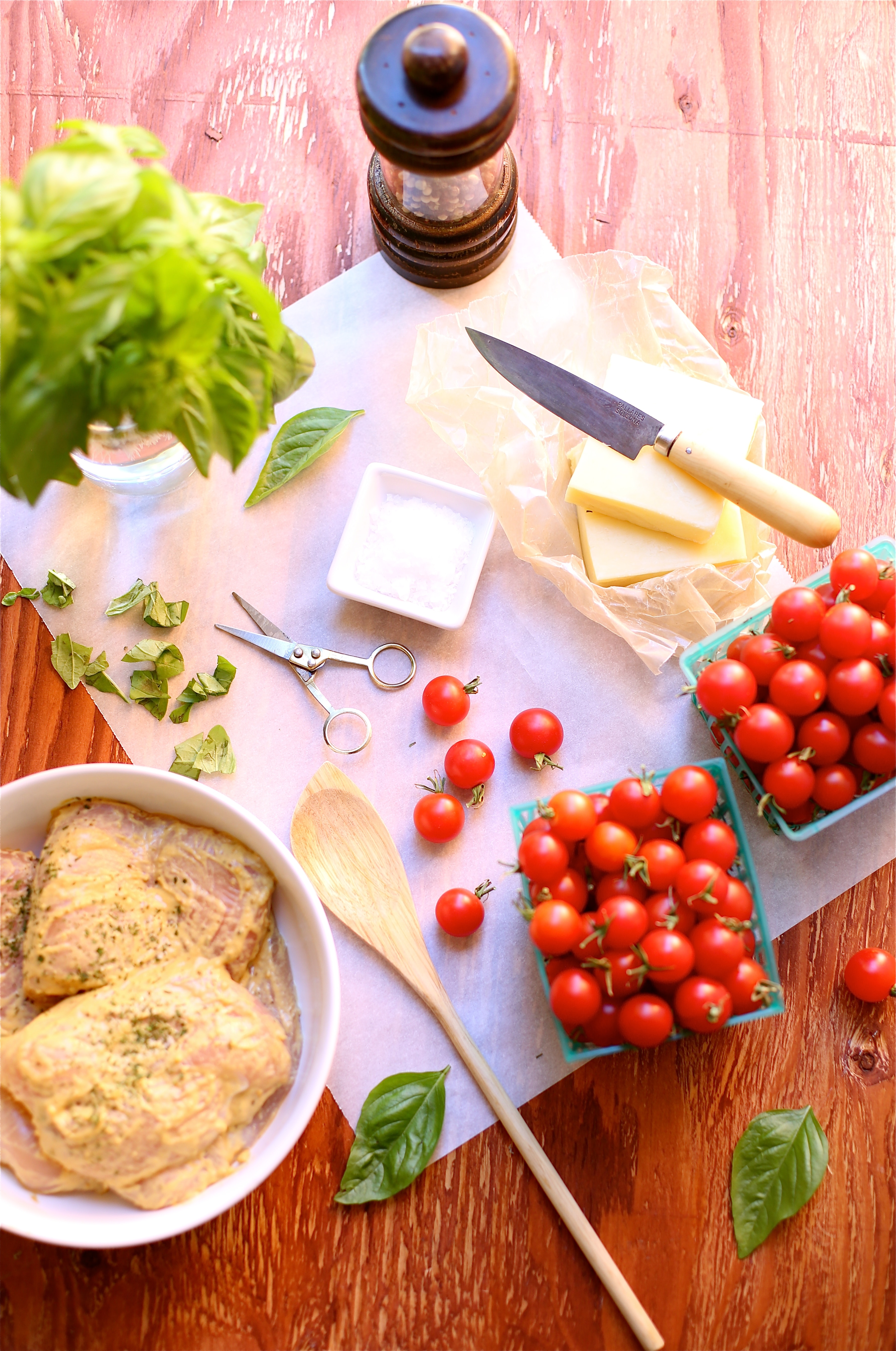 A photo of ingredients to be made into a meal:  chicken, tomatoes, basil, cheese, seasonings.