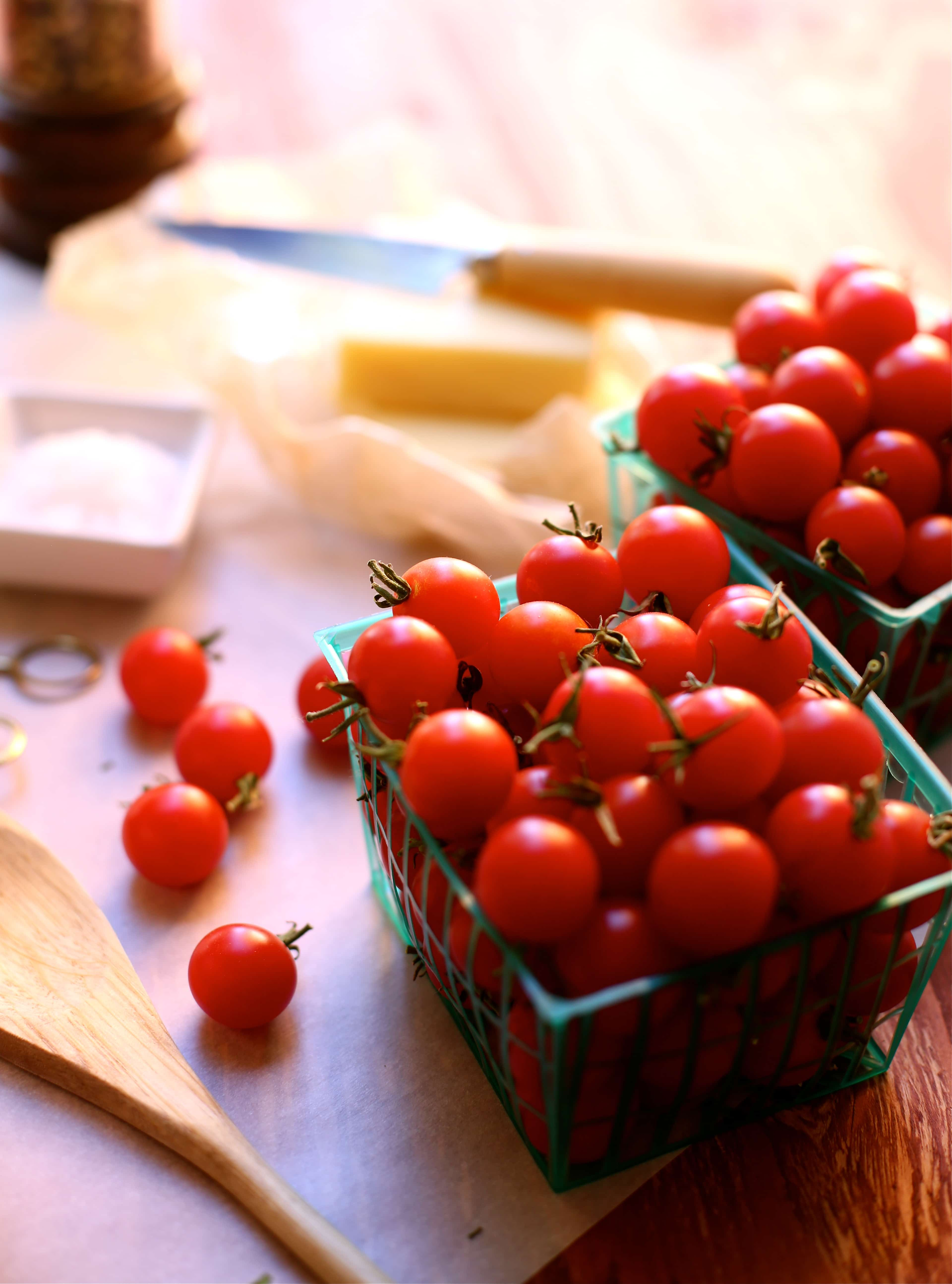 small greeen crates of red cherry tomatoes with a wooden spoon alongside, knife and cheese in the background.