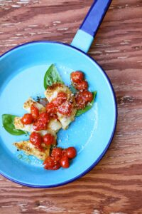 chicken and tomatoes in aa blue saute pan