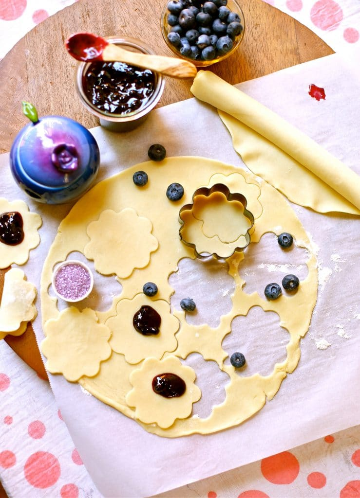 Ingredients for Easy Little Lemon Blueberry Pies jam, blueberrys crust, a cookie cutter and wooden spoon