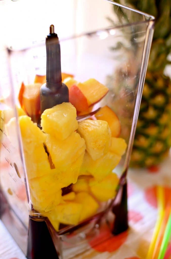 Fresh pineapple and nectarines cut in cubes in a blender with pineapple in the background