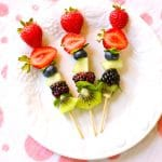 three fruit skewers on a white plate