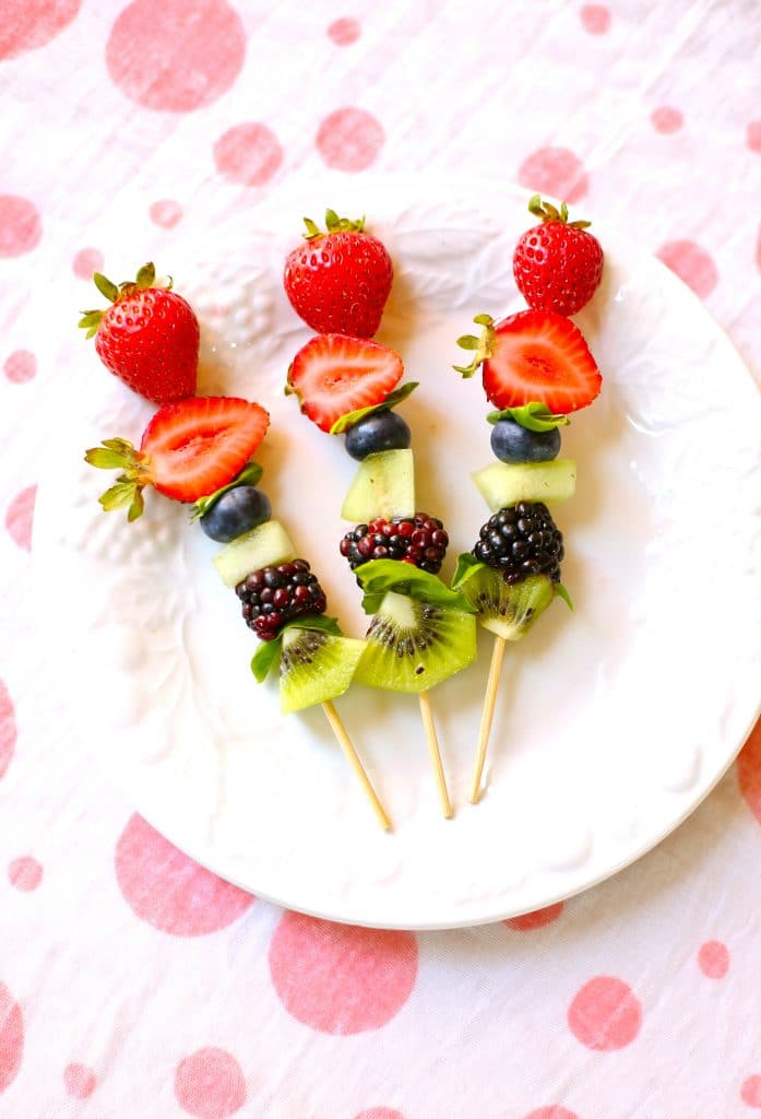 Three fresh fruit kabobs, strawberry, blueberry, melon, blackberry and kiwi on a wooden skewer, on a white plate on a polka dotted tablecloth