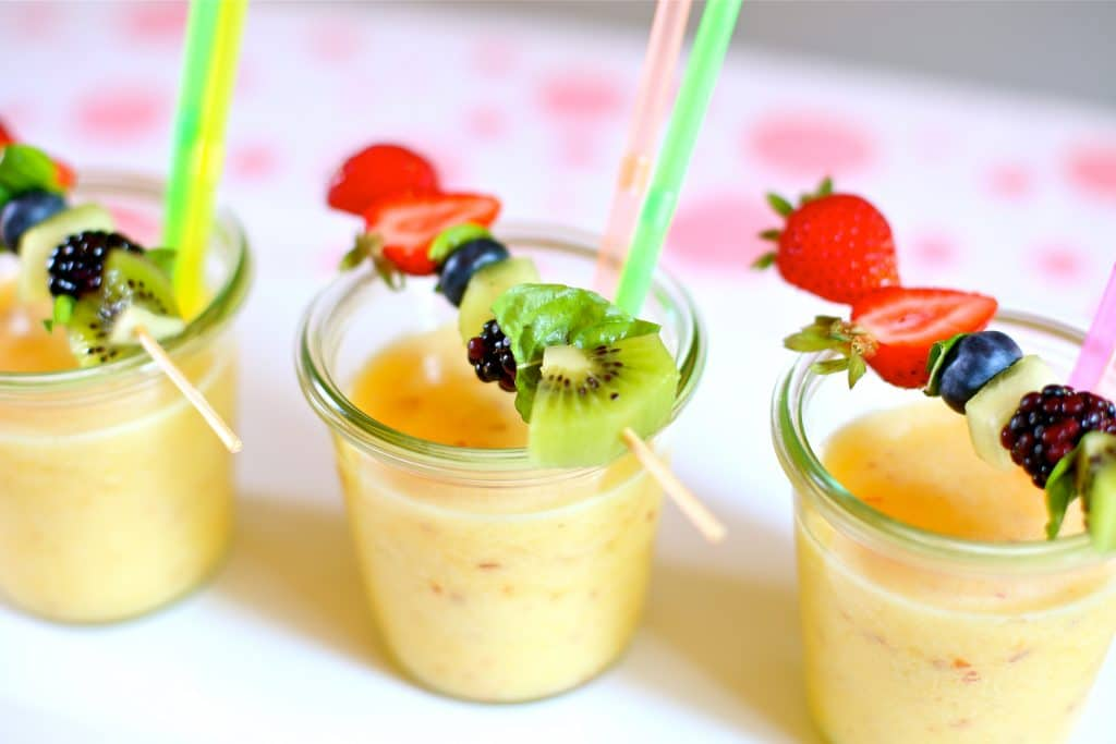Three Frozen Pineapple Nectarine Slushee's with fresh fruit kabobs on top