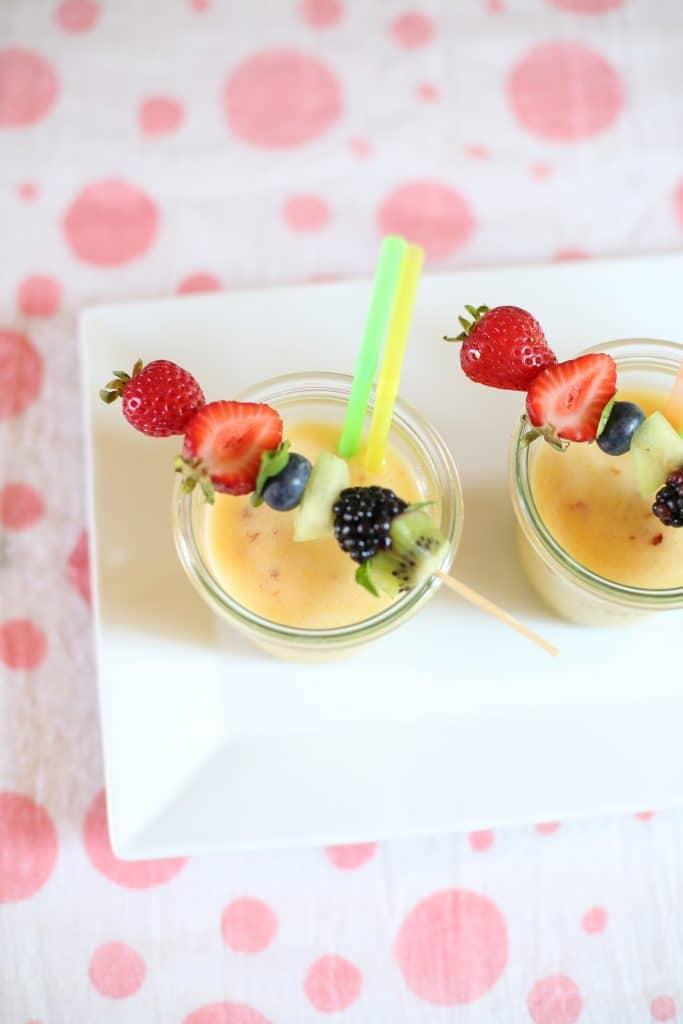 Frozen Pineapple Nectarine Slushee's on a white plate and polka dot background
