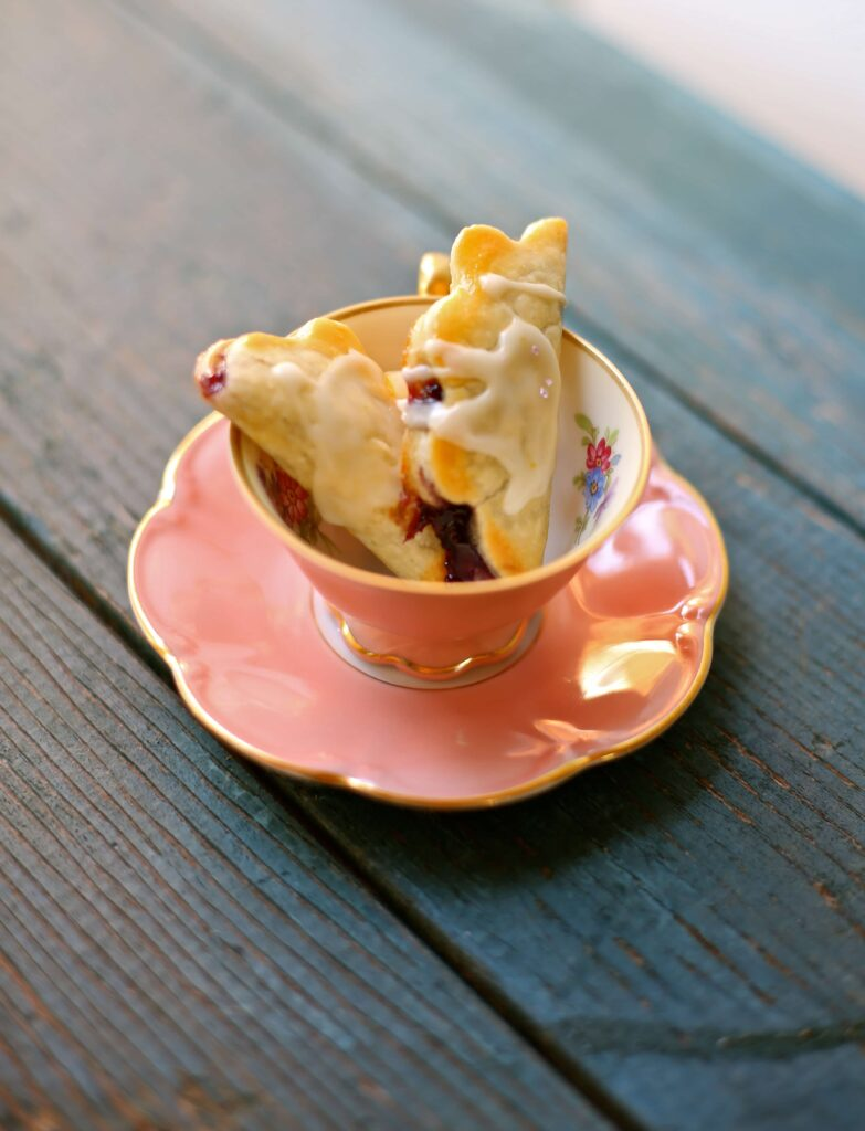 Easy Little Lemon Blueberry Pies in a pink teacup on a blue wooden background