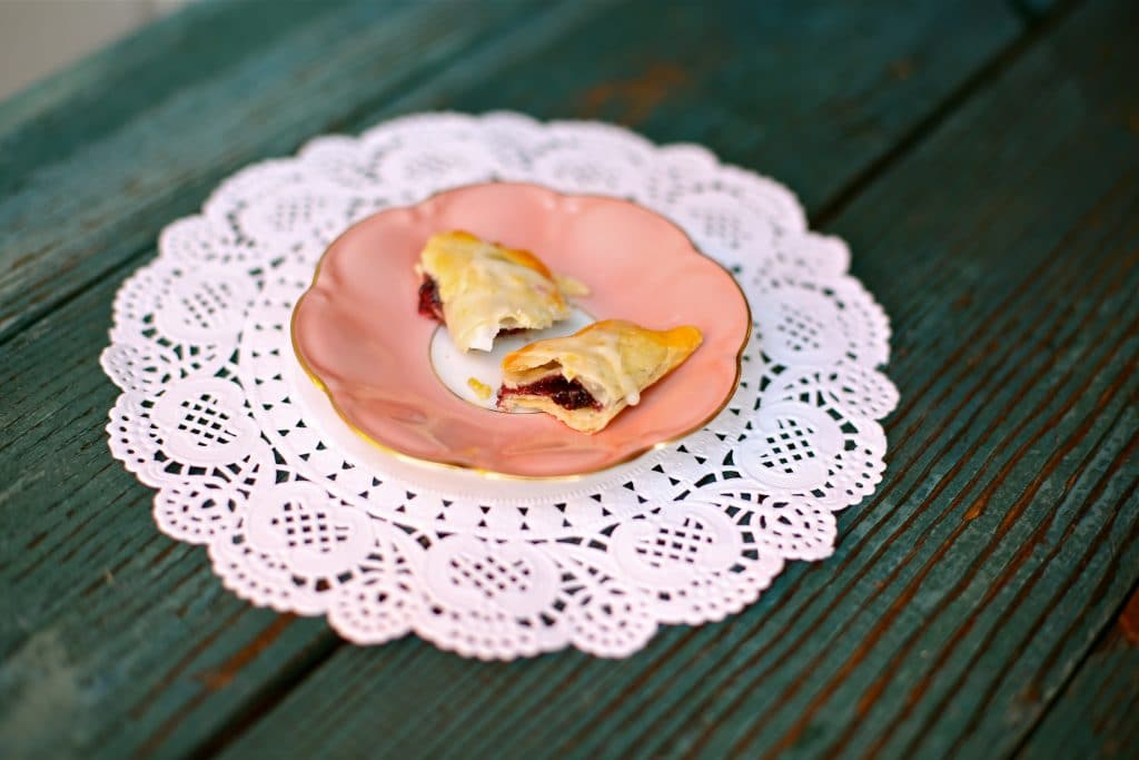 Easy Little Lemon Blueberry Pies on a pink plate with white doily and blue background