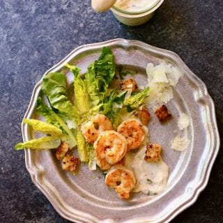 salad with shrimp on a silver platter and dark gray board