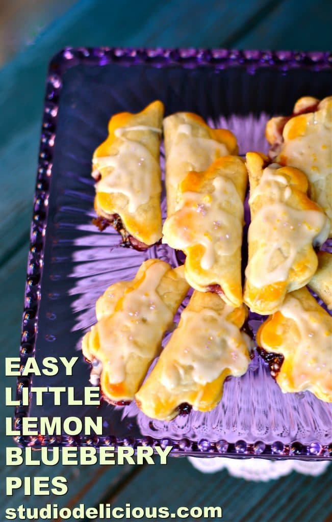 Easy Little Lemon Blueberry Pies with text that says that and pies are on purple glass platter with blue background