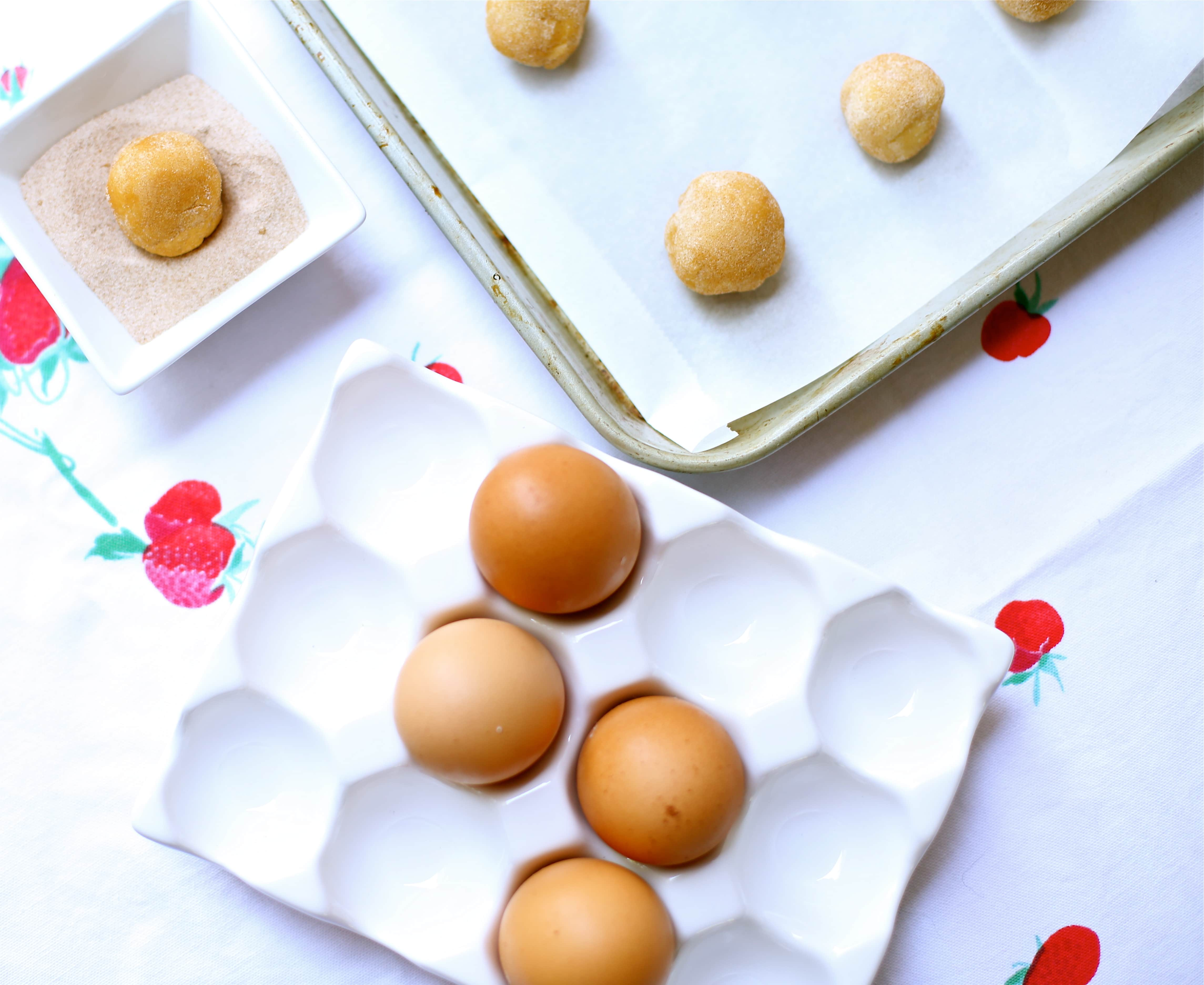 eggs in a crate and cookies on a sheet tray and a cookie in cinnamon sugar waiting to be baked