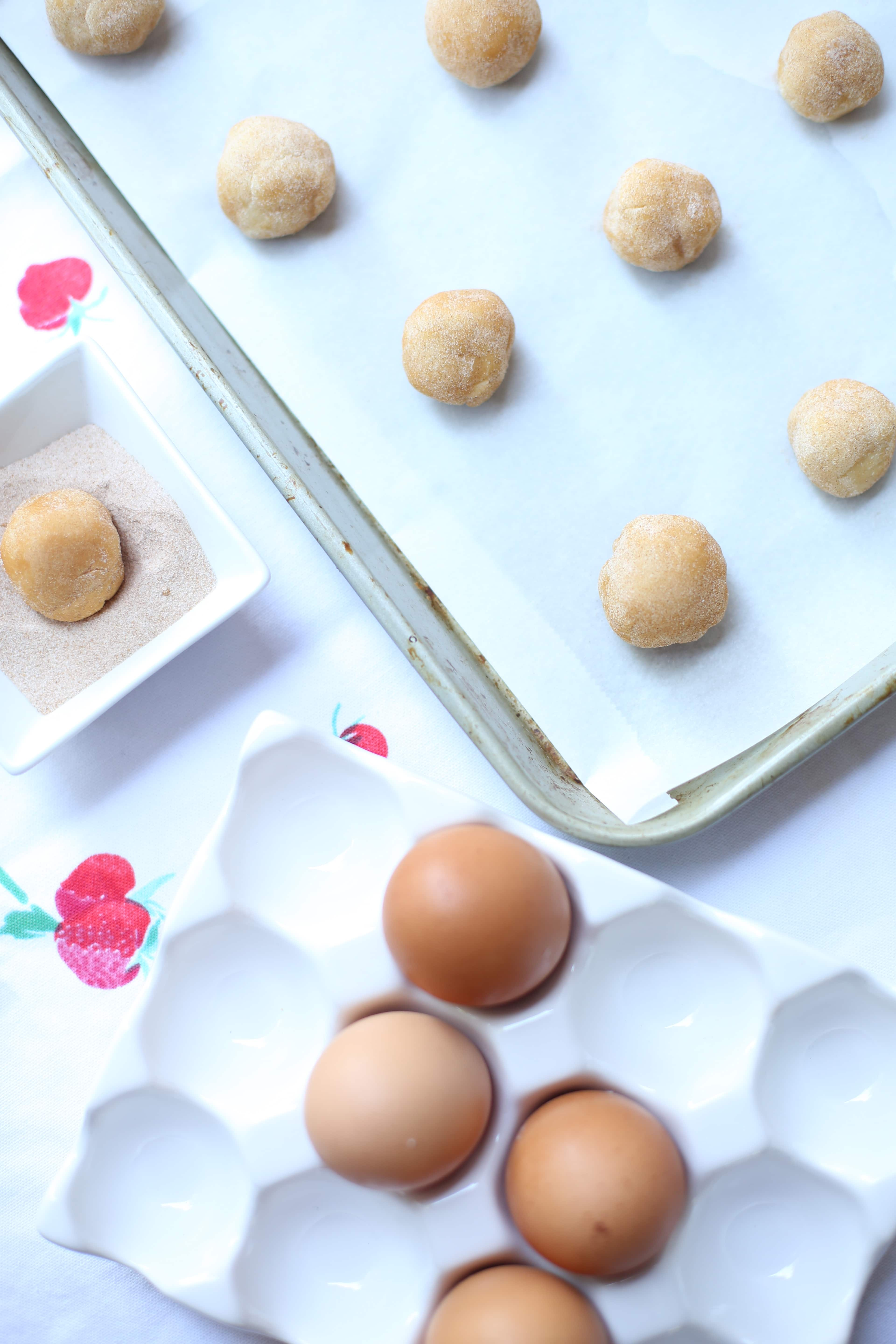 unbaked cookies on a tray and some fresh eggs in a white crate