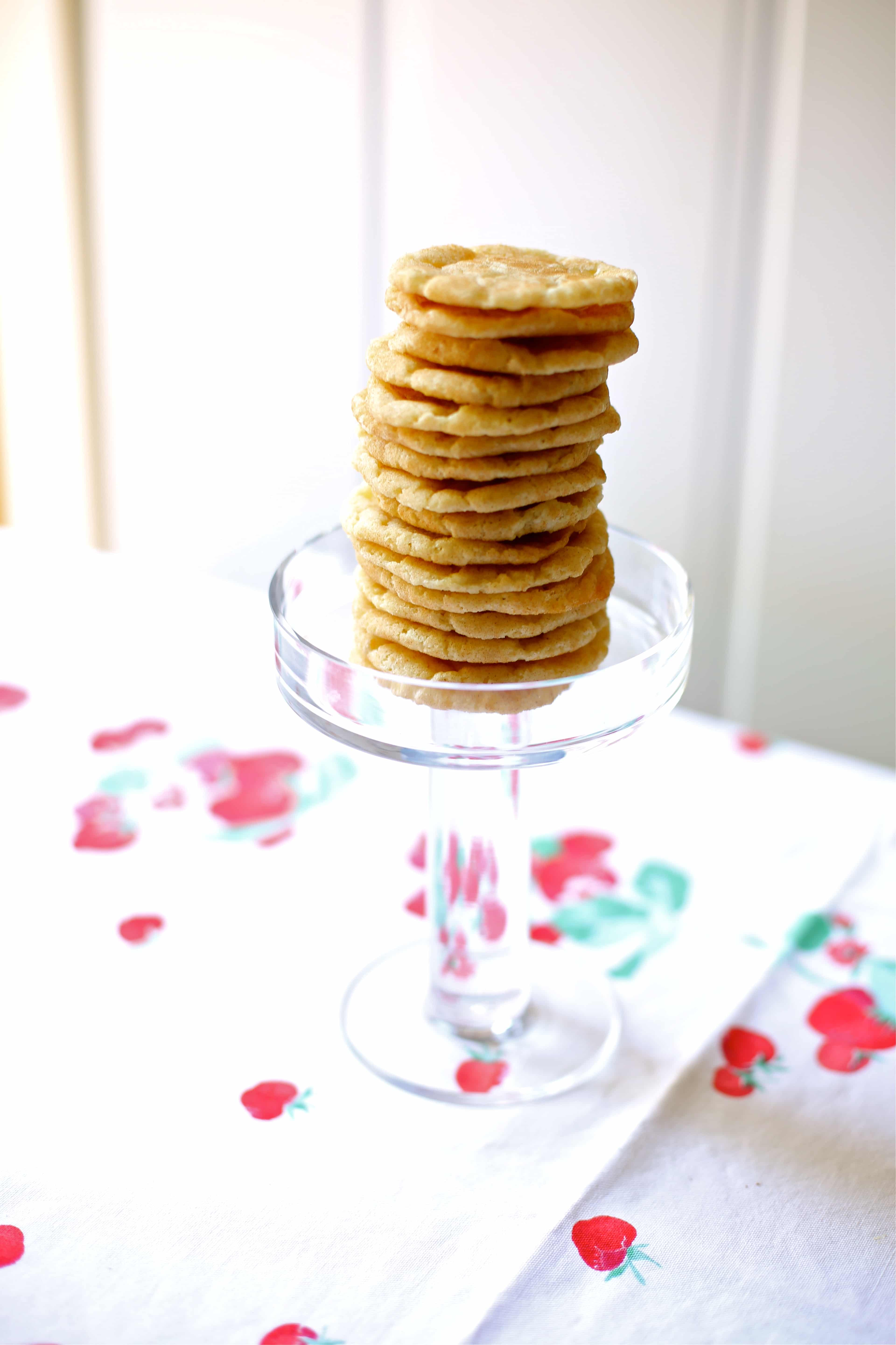a tower of cookies on a glass tray on a tablecloth