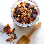 trail mix in a container with a wooden spoon