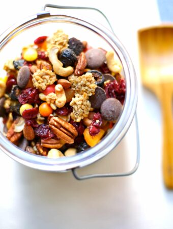 trail mix in a container with wooden spoon