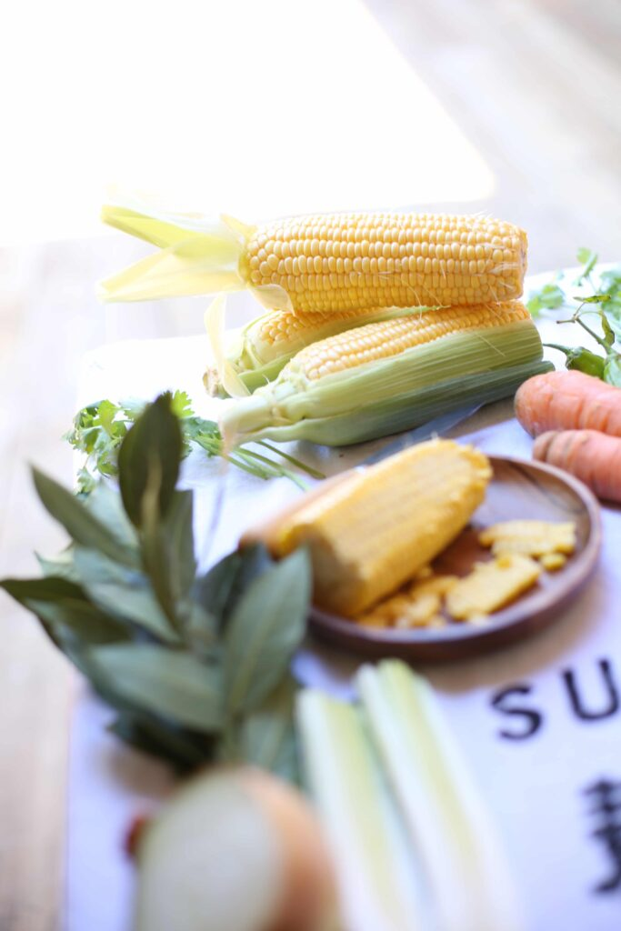 Fresh Corn shucked on a plate and other ingredients for Fresh Corn Chowder