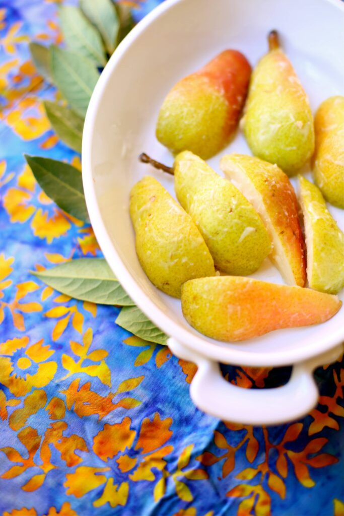 Sliced pears in a white casserole dish with leaves and a gold and blue tablecloth